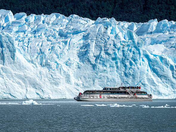 Tourist boat in front a this stunning glacier wall